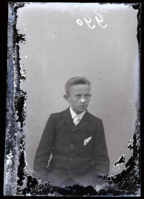 Zittend portret van jongeman in feestkledij bestaande uit kostuum, wit hemd met stropdas en pochdoekje in linker bovenzakje, kuifvormig naar rechts gekamd haar , Melle, 1910-1920
