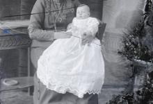 Zittend portret, jonge vrouw met opgestoken haar, halsketting, met baby op de schoot, Melle, 1910-1920