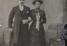 Staand studiofoto, koppel in feestkledij, man met lange jas en witte vlinderdas, vrouw met halsketting en bloementuiltje in de hand, Melle , 1910-1920