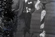 Staande foto van jongeman in feestkledij met wit hemd en vlinderdas, bloem op de boord, boek in de linkerhand, tgv Pl.Communie, Melle , 1910-1920
