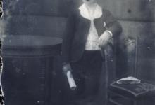 Rechtstaande foto van jongeman in feestkledij met wit hemd en witte kraag, kortgeknipt haar, opgerold document in rechterhand, Melle , 1910-1920