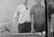 Staande foto van 2 jonge mannen, opgerolde mouwen, troskoord als stropdas, naar voor gekamd haar, Melle , 1910-1920