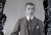 Staande foto van jonge man met kostuum, wit hemd en stropdas, kort geknipt haar, ketting voor borstuurwerk, Melle , 1910-1920