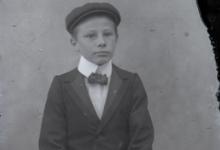 Zittend portret van jongen in kostuum met wit hemd en vlinderdas, pet als hoofddeksel, Melle , 1910-1920