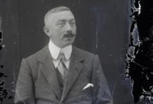 Zittend portret van man in kostuum en wit hemd met stropdas, gemodelleerde snor en strak gekamd haar, Melle , 1910-1920