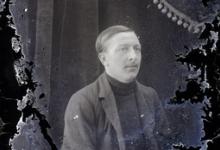 Zittend portret man van middelbare leeftijd met vest en gestreepte pullover met hoge kraag, strak opzijgekamd haar, Melle , 1910-1920