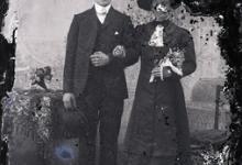 Staand portret van een koppel in feestkledij, man in kostuum met wit hemd en witte vlinderdas en strak gekamd haar, bolhoed in de hand, vrouw met hoed en boementuiltje in de linkerhand , Melle , 1910-1920