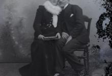 Zittend portret van een koppel in feestkledij, man in kostuum en witte hemdskraag en pochdoekje in bovenste vestzak, vrouw in lang kleed met vestje en witte vellen kraag, Melle, 1910-1920