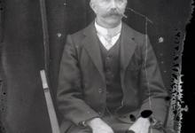 Zittend portret van man in feestkledij met kostuum en witte opstaande hemdskraag met stropdas, gemodelleerde snor en hoofdhaar met middenscheiding, Melle, 1910-1920