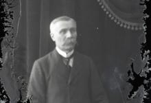 Zittend portret van man in feestkledij met wit hemd en stropdas, gemodelleerde snor en glad naar rechts gekamd haar, Melle, 1910-1920
