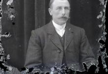 Zittend portret van man in feestkledij met witte hemdsboord en stropdas, gemodelleerde snor en en strak naar rechts gekamd haar, Melle, 1910-1920