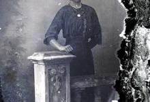 Staand portret van jonge vrouw in feestkledij bestaande uit lange rok en bloes met driekwart mouwen en witte halskraag, halsketting met muntstuk, Melle, 1910-1920