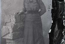 Staand portret van jonge vrouw in feestkledij bestaande uit lang kleed met brede heupband en driekwart mouwen, opgestoken haar, Melle, 1910-1920