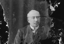 Zittend portret van man in feestkledij bestaande uit kostuum en wit hemd met stropdas, gemodelleerde snor, Melle, 1910-1920