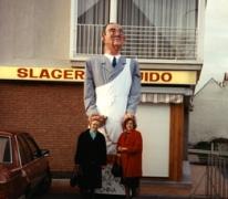 De dochters van Raymond Wollaert, Gisèle en Angéle bij de reus Mondje Wollaert voor de slagerij, Merelbeke, 1990.