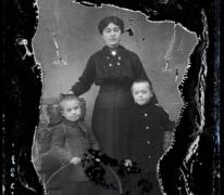 Staand portret, jonge vrouw in donkere kledij, 2 kinderen met kort genipt haar, Melle, 1910-1920