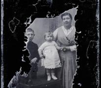 Staand portret, jonge vrouw met kleed in fijn geruite stof, 2 kinderen, 1 jongen en 1 meisje +/- 10 en 3 jaar, Melle, 1910-1920