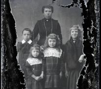Staand portret, vrouw in feestkledij met halsketting, 3 meisjes met haarstrik, 1 jongen met witte kraag, Melle, 1910-1920