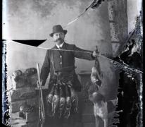 Staand portret, man met brede snor in jagerskostuum met geweer, jachthond en jachttrofeeën, Melle , 1910-1920