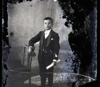 Staand portret, tiener in feestkledij, wit hemd en witte vlinderdas, lederen handschoenen, opgerold document in linkerhand, Melle , 1910-1920