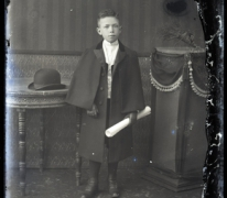 Staand portret van jongeman, feestkledij met lange mantel en lederen handschoenen, opgerold dokument in linkerhand, Melle , 1910-1920