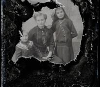 Foto van zittende moeder in feestkledij met lange halsketting, 2 jonge tienerdochters met lang haar en opgespelde strik, Melle , 1910-1920