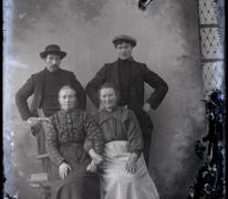 Studiofoto van 2 vrouwen in lange feestkledij en naar achter gekamd haar en 2 mannen in vest en donkere hoogsluitende  trui, beiden met een pijp in de mond, één met hoed en andere met pet, Melle , 1910-1920