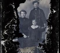 Staand familieportret 3 generaties, grootmoeder met donkere lange kledij en lange halsketting, moeder met opzij gekamd haar, 2 jonge kinderen, Melle , 1910-1920