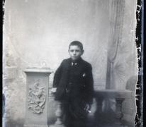 Staand portret tienerjongen in feestkledij en stropdas, korte haarsnit en sigaret in hand, Melle , 1910-1920