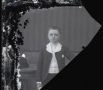 Staande portret jongen in feestkledij, Pl.Communie, kort geknipt rechtopstaand haar, opgerold document in rechterhand , Melle , 1910-1920