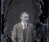 Zittend portret, man van middelbare leeftijd in feestkostuum met wit hemd en stropdas, gemodelleerde snor en strak naar achter gekamd haar, Melle , 1910-1920