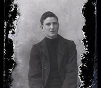 Zittend portret van jongeman in kostuum met halsdichte pullover, kuifvormig gekamd haar met linkerscheiding, Melle , 1910-1920