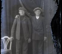 Staand portret van 2 jonge mannen in kostuum en hoofddeksel, 1 in wit hemd zonder opstaande boord en 1 in donkere pullover, Melle , 1910-1920