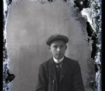 Zittend portret van jonge man in kostuum met wit hemd en stropdas, hoofddeksel, Melle , 1910-1920