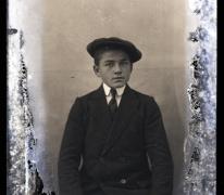 Zittend portret van jonge man in feestkledij met wit hemd stropdas en pet, Melle , 1910-1920