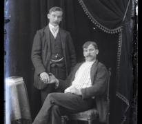 Portret van staande man in feestkledij met wit hemd en stropdas en zittende man, beiden met snor en kuifvormig gekamd haar , Melle , 1910-1920