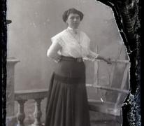 Staand portret van jonge vrouw in feestkledij bestaande uit lange rok en witte bloes, opgestoken haar met insteekkam, Melle , 1910-1920
