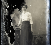 Staand portret van jonge vrouw in feestkledij bestaande uit lange rok en witte bloes met driekwart mouwen, opgestoken haar, Melle , 1910-1920