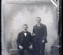Portret van 1 staande en 1 zittende man in feestkledij zijnde kostuum en wit hemd met stropdas en vlinderdas, Melle , 1910-1920