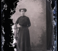 Staand portret van jonge vrouw in lange feestkledij met lange halsketting en golvend gekruld opgestoken haar, Melle, 1910-1920