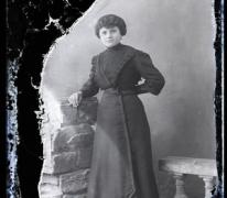 Staand portret van jonge vrouw in donkere feestkledij met golvend opgestoken haar, Melle, 1910-1920
