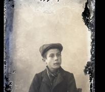 Zittend portret van jonge man in feestkledij met vest en sjaal om de hals, pet op het hoofd, Melle, 1910-1920