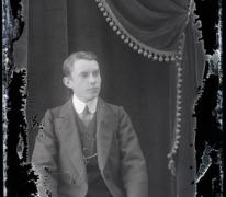 Zittend portret van jonge man in feestkledij met kostuum en witte hemdskraag met stropdas, kuifvormig naar links gekamd haar, Melle, 1910-1920