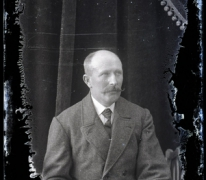 Zittend portret van man in feestkledij met witte hemdsboord en donkere stropdas, gemodelleerde snor en kalend voorhoofd, Melle, 1910-1920