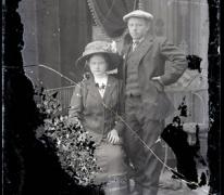 Portret van koppel in feestkledij, zittende vrouw met lange rok en vest, versierde bloeskraag, lange halsketting en opgespelde bloem en bloemversierde hoed, rechtstaande man in kostuum met hemd en stropdas, hoofddeksel, Melle, 1910-1920