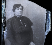 Zittend portret vrouw in donkere feestkledij, opgemaakt haar en borstketting, Melle, 1910-1920