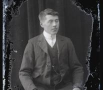 Zittend portret van jonge man in feestkledij bestaande uit kostuum met wit hemd en fijne stropdas, golvend haar zijwaarts naar links gekamd, Melle, 1910-1920