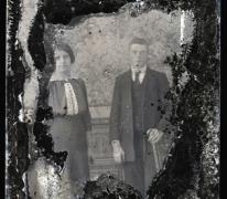 Staand portret van koppel in feestkledij bestaande uit(man) kostuum met wit hemd en stropdas, kort geknipt en naar achter gekamd haar,(vrouw) donkere lange rok en bloes met witte kraag en borststuk, opgemaakt haar, Melle, 1910-1920