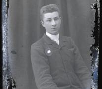 Zittend portret van jonge man in feestkledij bestaande uit kostuum, wit hemd en stropdas, kuifvormig naar achter gekamd haar, Melle, 1910-1920