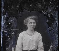 Zittend portret van jonge vrouw in feestkledij bestaande uit lange rok en geborduurde bloes, armband en halsketting, opgestoken haar , Melle, 1910-1920
